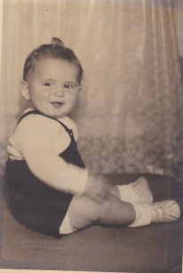 Small black and white personal picture of me as a baby with a tiny curl of hair on the top of my head