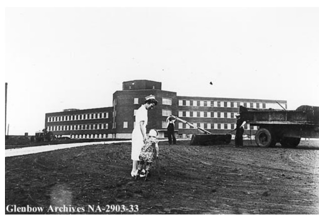 1959 Black and white picture of the Alberta Children's Hospital with a nurse in the foreground taking a young patient for a walk while a landscaper in the background prepares to lay turf