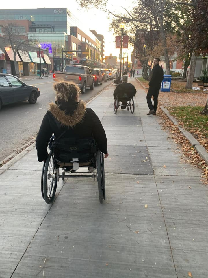 A picture of one group member trying to keep up with me in my wheelchair being completely oblivious to the lag in distance between us.
