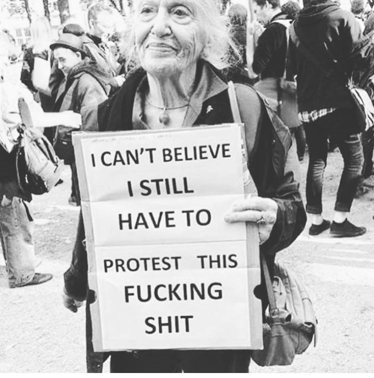"""A black and white picture of an elderly lady holding a sign reading """"I can't believe I still have to protest this fucking shit"""""""