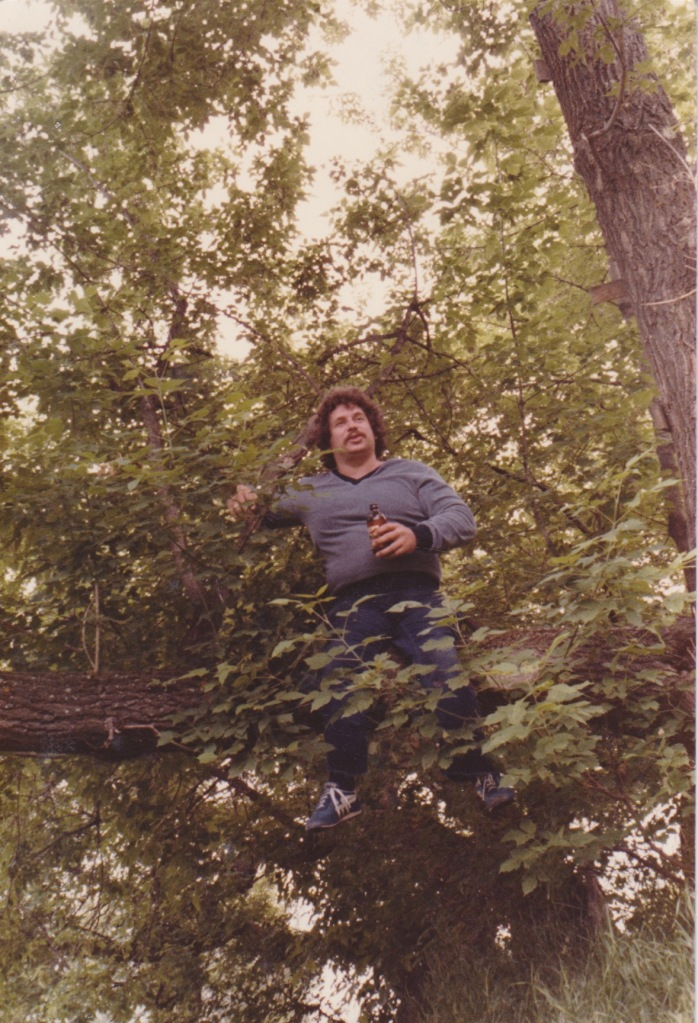 "A simple picture of me sitting in a tree with a beer in my one hand and a joint in the other circa 1981 Pigeon Lake Cabin, caption ""Life in a Tree"""